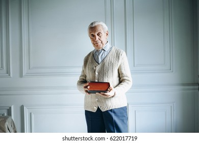 Old man holds a bible in his hands.