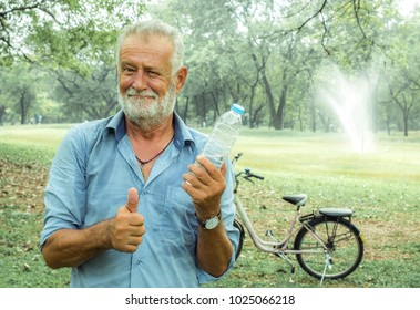 Old Man holds a water bottle with thumbs up in the park, the concept of an active lifestyle in old age, Drink healthy water