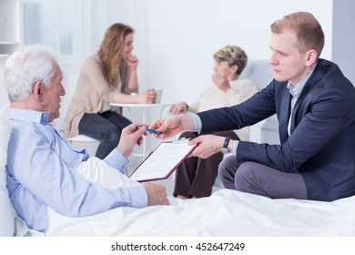 Old man in a hospital bed being handed documents to sign by a lawyer sitting next to him