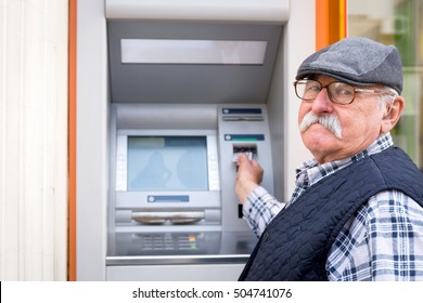 old man inserting credit card to ATM