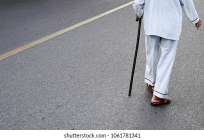 Old man with an invalid stick walking along the road