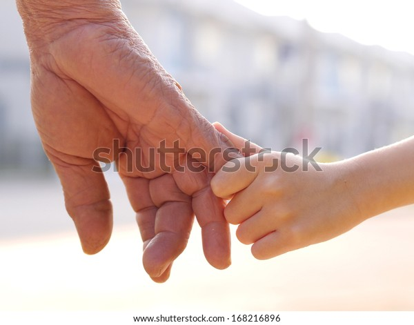 old man and a kid holding hands together