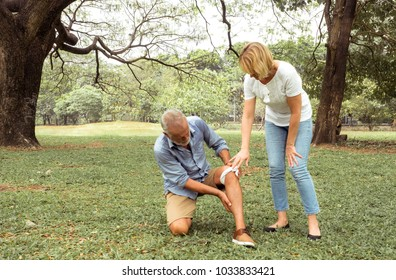 Old man with knee pain and women take care of him. Get first aid