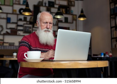 old man with a laptop in a cafe