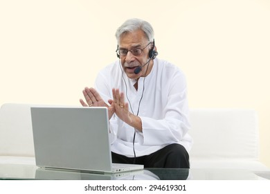 Old man with a laptop chatting online