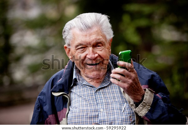 An old man laughing and smiling with a cell phone.