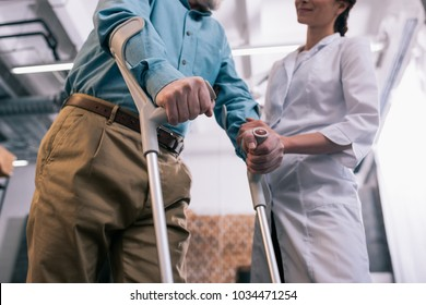 Old man leaning on crutches and female doctor hand
