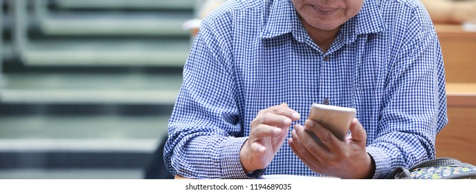 The old man is learning to use the application in the smart phone with blur background , in concept of information technology, edutainment, connection.