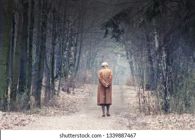 The old man leaves the road among the trees. Abstract aging, people of retirement age, passing time, lived life. The youth does not return. Loneliness and near death. Soon end of life.