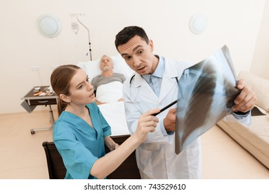 The old man lies on a cot in the medical ward, and next to him there is a doctor and a nurse. The doctor is holding an X-ray in his hands, the nurse is standing next to him. They are in modern clinic.