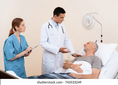 The old man lies on a cot in the medical ward. Next to him is a doctor and a nurse. The nurse writes down the old man's testimony, the doctor asks about his condition.