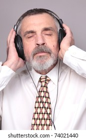 Old man listen music isolated against grey background.