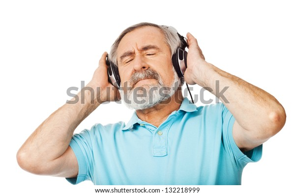 Old man listening to music with headphones on white background