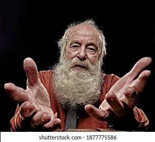 An old man with a long gray beard stretches out his palms to the camera and looks sadly. Studio portrait on a black background. Old age.