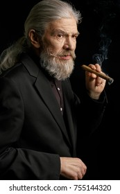 Old man with long grey hair holding cigar. Beardy aged man in dark suit against black background.
