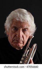Old man with long white hair holding a silver trumpet against a black background