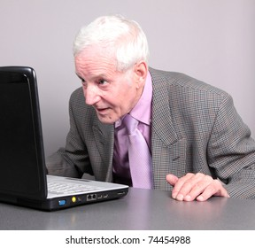 Old man look at monitor notebook isolated against grey background