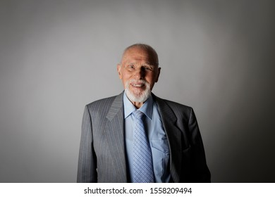 Old man looking at the camera. Portrait of a bearded old man. Senior man is smiling.
