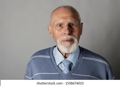 Old man looking at the camera. Portrait of a bearded old man. Senior man.