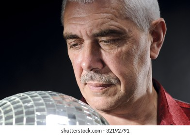 old man looking at discoball isolated on black
