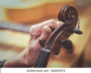 An old man (luthier) with aged hands is tuning a violin. You see other instruments like a guitar blurred in the background.