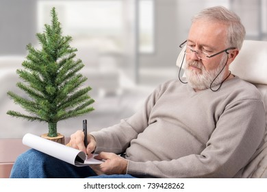 Old man making a shopping list with a pen on paper next to an undecorated fir tree for Christmas holidays
