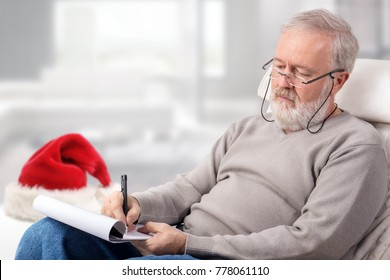 Old man making a shopping list with a pen on paper for holidays next to a red hat