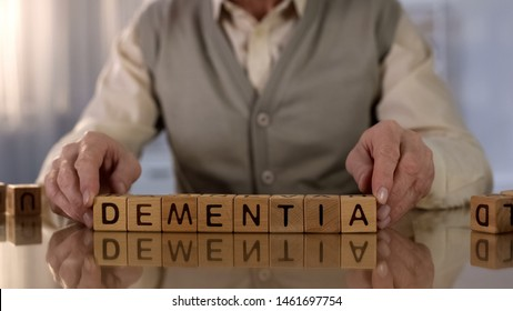 Old man making word dementia of wooden cubes on table, brain disease, health