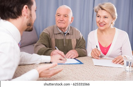 Old man and mature woman with social department manager fill in questionnaire