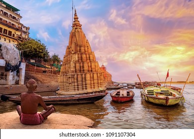 Old man meditates at Varanasi Ganges river bank at sunrise with view of wooden boats and ancient architecture.
