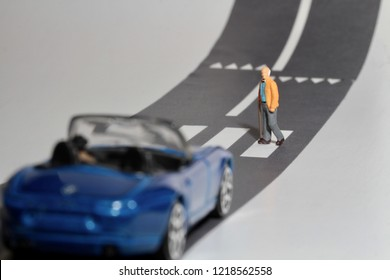 old man in miniature crossing an urban road