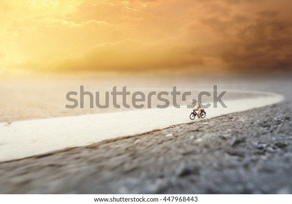 An old man (miniature) on cycle ride in country road .Soft Focus and Shallow Depth of Field Composition with Soft Pastel Color Theme.