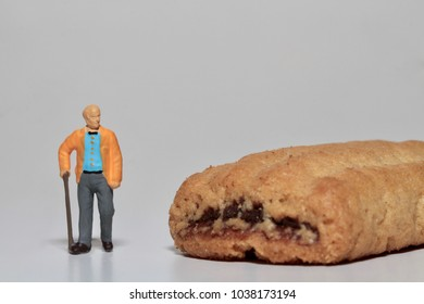 old man in miniature with a sweet cookie