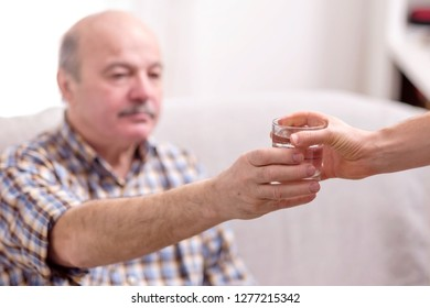 Old man with mustache receiving a glass of water from nurse. He is thirsty.