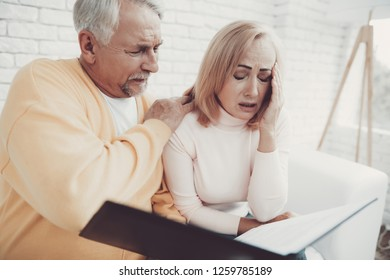 Old Man near Old Woman with Documents in Black Folder. Important Documents. Sitting on White Sofa. Grandfather and Grandmother. Family at Home. Reading Documents. People with Gray Hair.