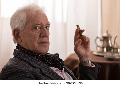 Old man is nostalgic and he is smoking a cigar