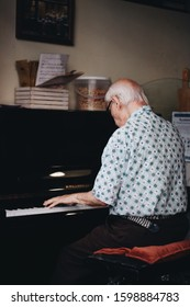 Old man on his back playing piano