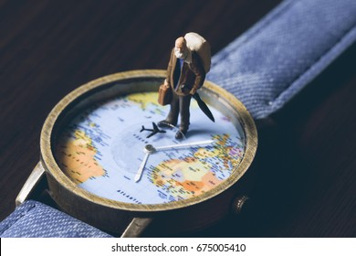 Old man on watches with world map, vintage toned photo. World travel banner. Senior traveler figurine. World time zones. Travelling around world concept. Senior age travel. Time of life in vacation