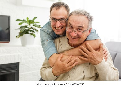 The old man on a wheelchair and his son . A man hugs his elderly father. They are happy and smiling