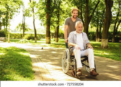 The old man on a wheelchair and his adult son are walking in the park. A man is assisting his father, they are having fun and they are laughing