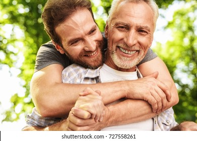 The old man on a wheelchair and his son are walking in the park. A man hugs his elderly father. They are happy and smiling