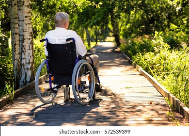 old man on wheelchair with tablet in hands sitting in the park
