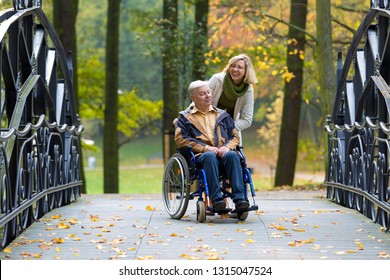 old man on wheelchair and young woman in the park in autumn