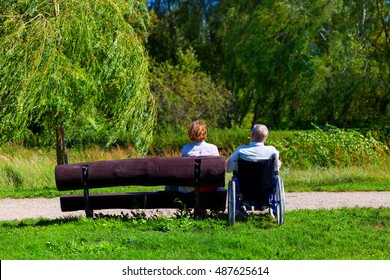 old man on wheelchair and young woman on a bench sitting in the park