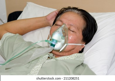 old man patient lying on hospital bed with oxygen mask