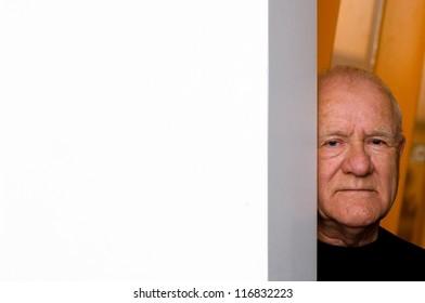 Old man peeking from behind a corner