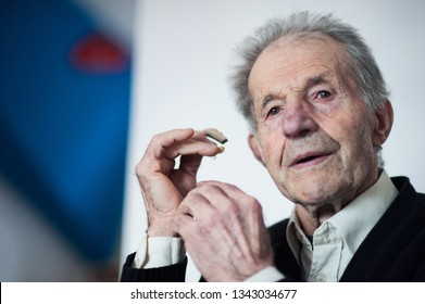 Old man placing hearing device into his ear