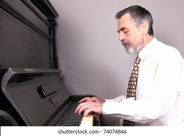 Old man play on piano. isolated against grey background
