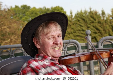 old man is playing violin on his balcony