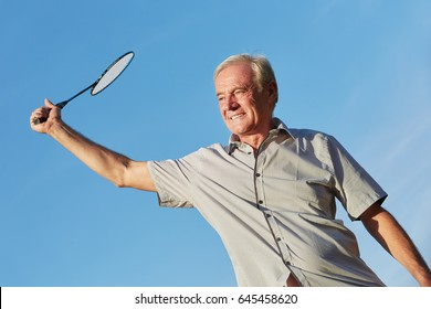 Old man plays badminton in summer in the nature